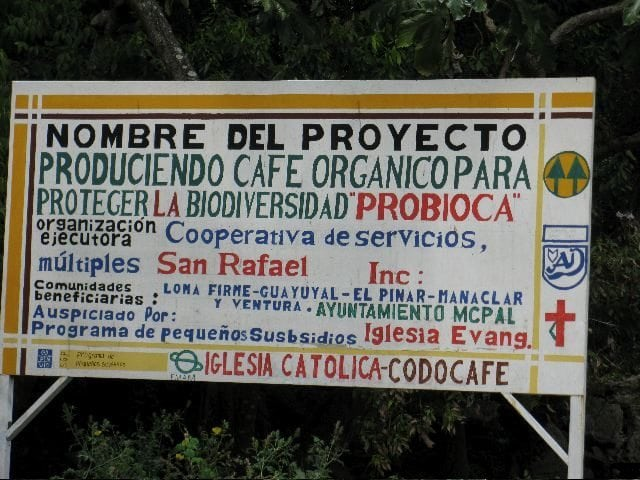 Road sign for the San Raphael Cooperative indicating the member groups and two of their core tenets, organic growing and biodiversity preservation. Photo by Barth Anderson.